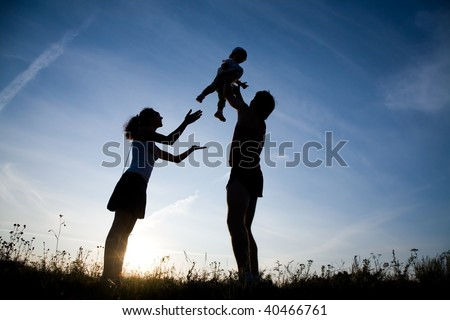 Young family happy play on the coast of background sunrise - stock photo