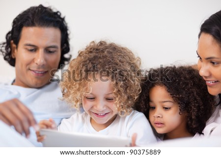 Young family having a joyful time in the bed