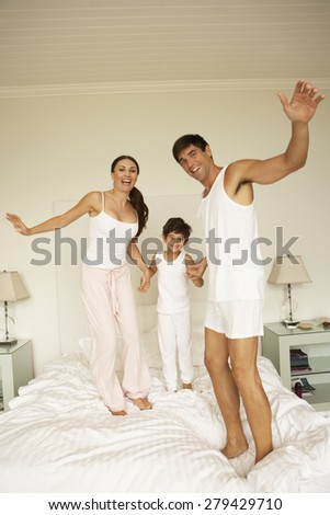 Young Family Having Fun Bouncing On Bed - stock photo