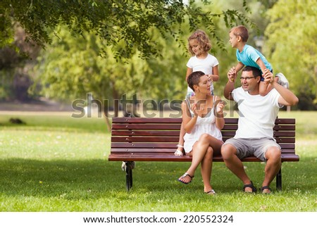 Young family having fun in a park together - stock photo