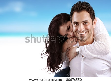 Young family having fun outdoors, handsome man carrying his girlfriend on the back, summertime vacation, love and romance concept - stock photo