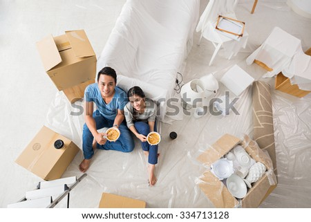 Young family having lunch after unpacking in new flat - stock photo
