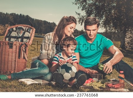 Young family having picnic outdoors  - stock photo