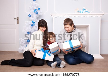 Young family holding gifts near the fireplace and Christmas tree. Christmas, New Year, holiday concept.