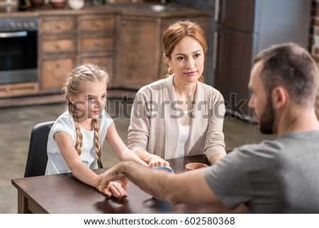 Young family holding hands while sitting at the table in kitchen