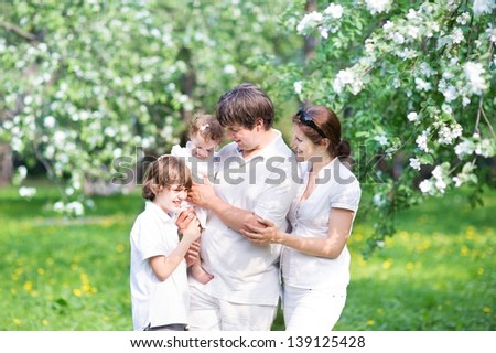 Young family in a beautiful apple tree garden