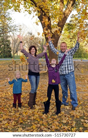 young family in autumn throwing leaves
