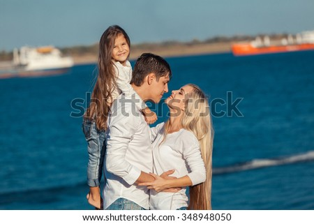 Young family in blue jeans hugging on the background of water. - stock photo