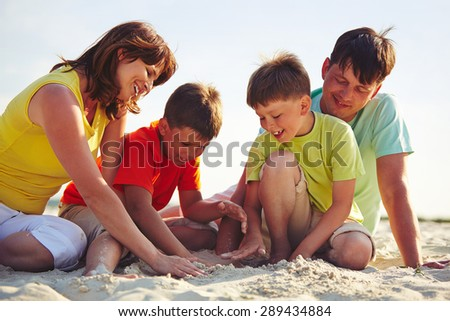 Young family in casualwear playing with sand on beach - stock photo