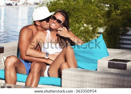 Young family in love feeling happy on the summer luxury resort, husband kissing wife. Vacations And Tourism Concept. - stock photo