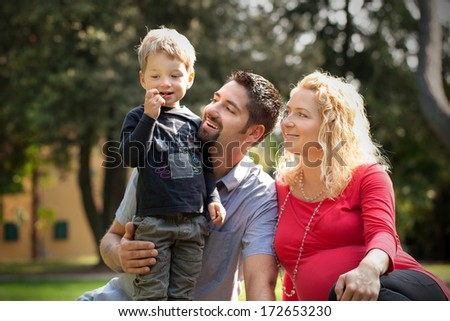 Young family in nature on sunny day - stock photo