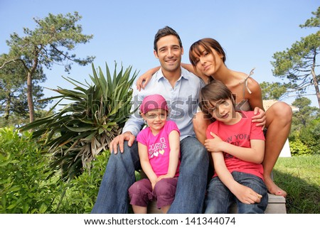 Young family in the garden - stock photo