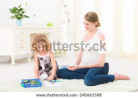 Young family is playing board-game Sitting on carpet and playing - stock photo