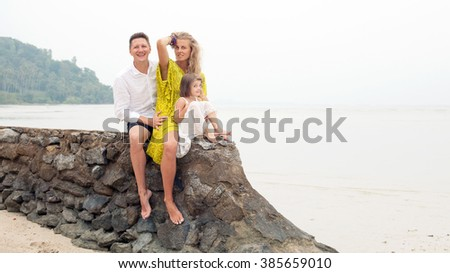 Young family is sitting on the wall on the tropical sea background.