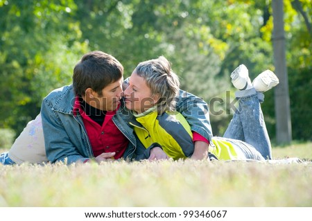 Young Family lad and girl pose in park by autumn