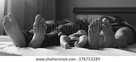 Young family lie on a bed feet to the viewer. The family consists of mother, father and little baby. Black-and-white background picture.