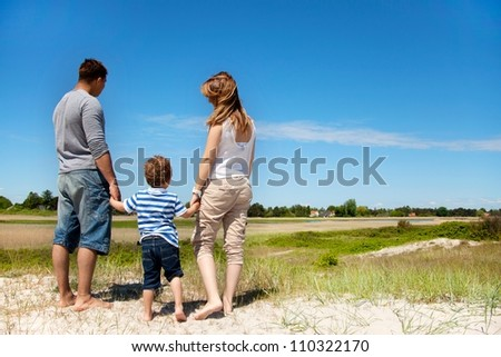 Young family looking and enjoying the beautiful landscape - stock photo