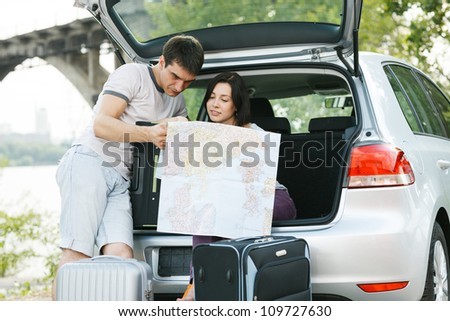 Young family looking at map near the car outdoors - stock photo