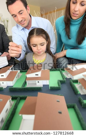 Young family looking at model housing - stock photo