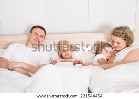 Young Family Lying Together In Bed At Home