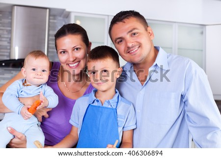 Young family making dinner together in the kitchen - stock photo