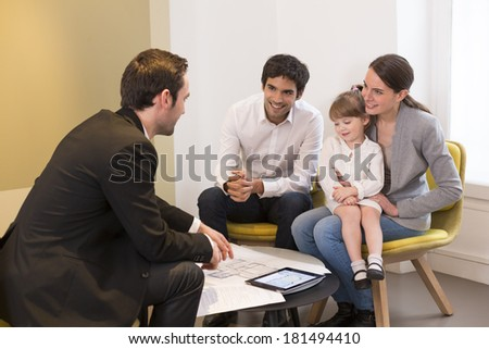 Young Family meeting real-estate agent to buy property - stock photo