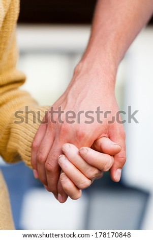 Young family member taking and elderly woman for a walk. - stock photo