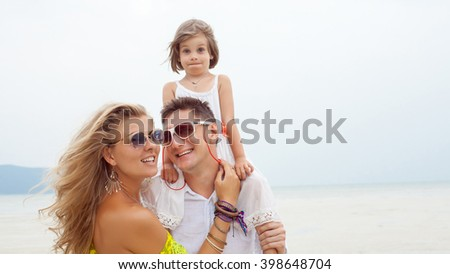 Young family of father, mother and daughter on the tropical sea background. - stock photo