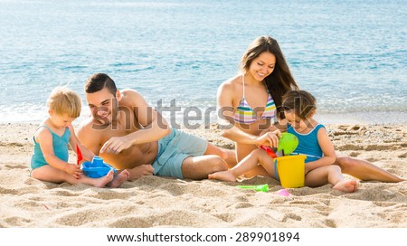 Young family of four people spending a weekend at the beach - stock photo