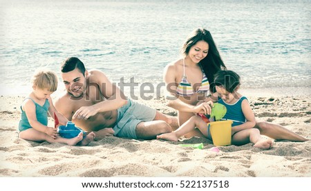 Young family of four people spending a weekend at the beach
