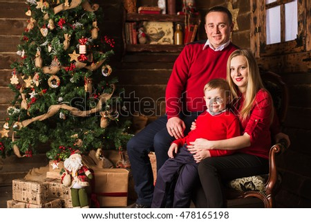 Young family of pregnant mother, father and little son celebrating Christmas at home with Christmas tree and presents on background. Christmas and New Year time celebration