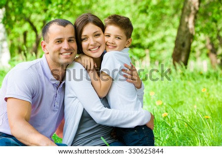 Young family of three has picnic in park. Concept of happy family relations and carefree leisure time