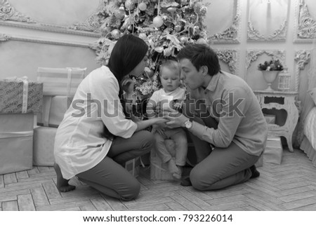 Young family on Christmas Eve blow out a candle - black and white