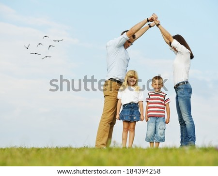 Young family on green summer grass meadow building dream new home - stock photo