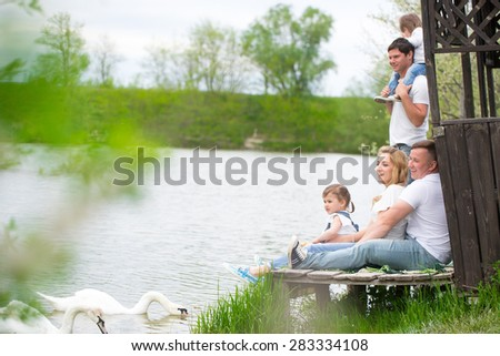Young family on picnic near the lake - stock photo