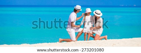 Young family on white beach during summer vacation - stock photo