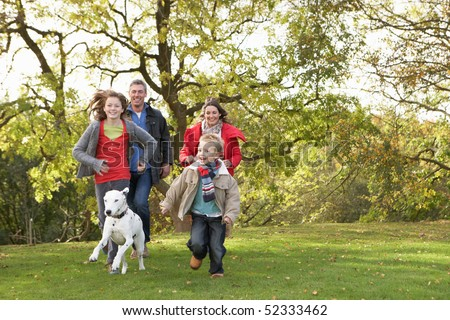 Young Family Outdoors Walking Through Park With Dog - stock photo