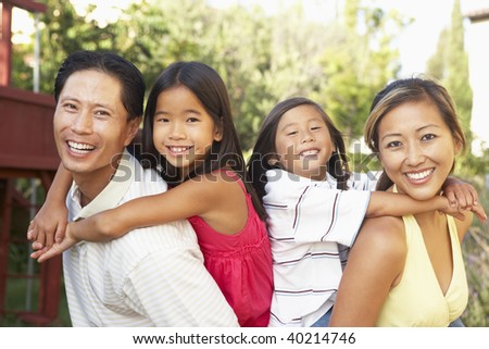 Young Family Playing In Garden Together - stock photo