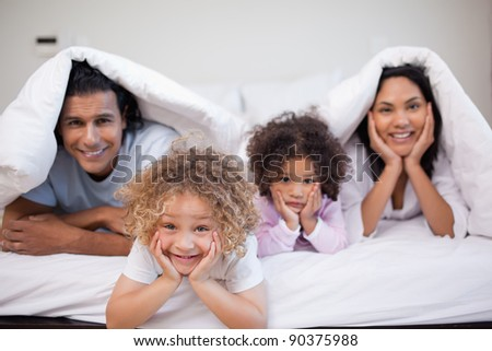Young family playing in the bedroom together - stock photo