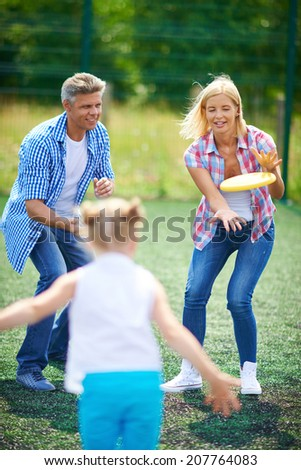 Young family playing with flying disc in the countryside