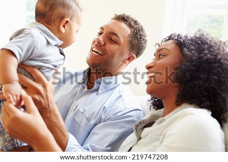 Young Family Playing With Happy Baby Son At Home - stock photo