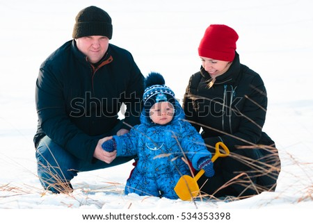 Young family playing with their child in the snow in the park