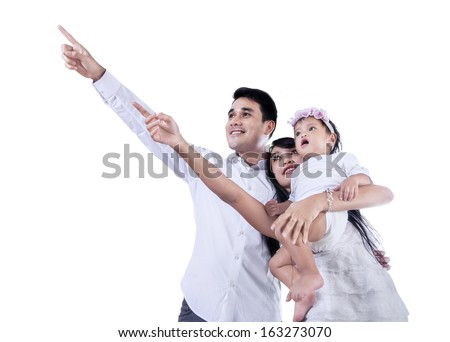 Young family pointing at copyspace - isolated on white background - stock photo