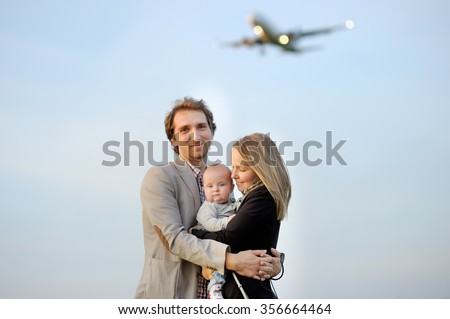 Young family portrait with airplane on background - stock photo