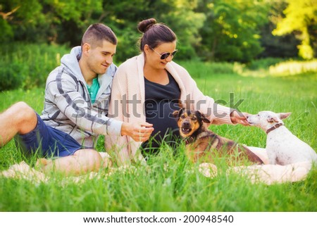 Young family / Pregnant couple playing with their pets