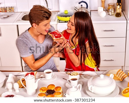 Young family  preparing and eating breakfast at home kitchen.