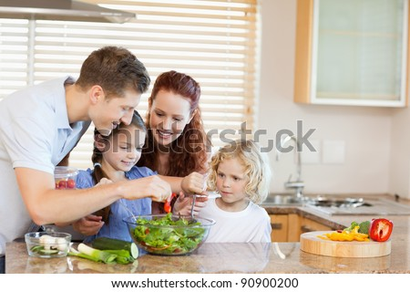 Young family preparing salad together - stock photo