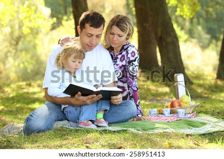 young family read the Bible in nature