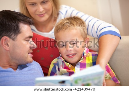 Young family reading a book together seated on the couch with their young son pointing to something on the page as the child smiles happily - stock photo