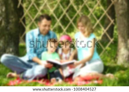 young family reading the Bible in nature